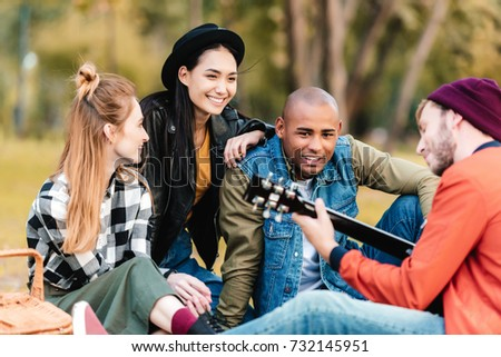 group of happy multicultural friends resting in park together #732145951