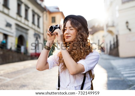 Beautiful young tourist with camera in the old town. #732149959