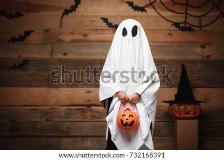 Halloween Concept - little white ghost with halloween pumpkin candy jar doing trick or treat with curved pumpkins over bats and spider web on Wooden studio background. Royalty-Free Stock Photo #732168391