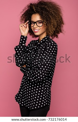 Portrait of the beautiful smiling black woman wear glasses and black shirt with white peas  #732176014