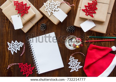 Preparation for the New Year holidays concept, gifts, New Year's decor, notebook, cup of hot chocolate, Santa Claus hat on a wooden background. Horizontal. Top view. #732214777