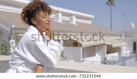 Young gentle girl with curls posing in white bathrobe on terrace of resort hotel leaning on fence with eyes closed and enjoying morning sunshine. #732231046