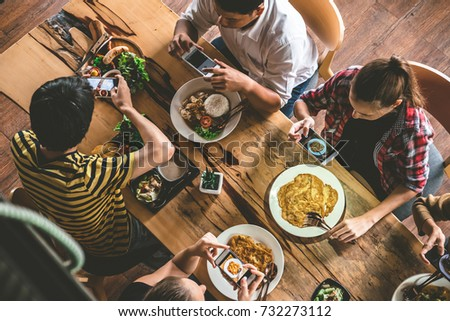 Group of friend take a picture with mobile phone before having nice food and drinks, enjoying the party and communication, Top view of Family gathering together at home for eating dinner.