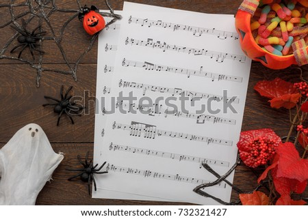 Top view of decorations Happy Halloween Festival and music notes paper background concept.The pumpkin and accessories  on modern brown rustic wooden at office desk.Mix variety object idea for season. #732321427