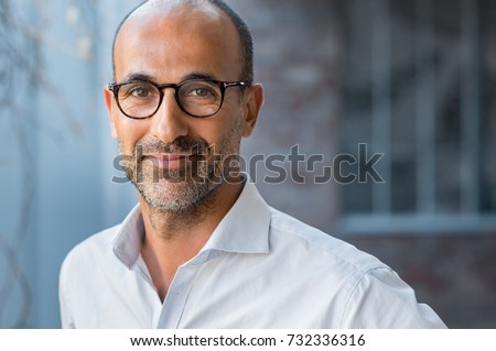 Portrait of happy mature man wearing spectacles and looking at camera outdoor. Man with beard and glasses feeling confident. Close up face of hispanic business man smiling. #732336316