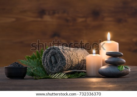 Towel on fern with candles and black hot stone on wooden background. Hot stone massage setting lit by candles. Massage therapy for one person with candle light. Beauty spa treatment and relax concept. #732336370