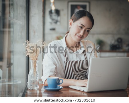 Asian woman working in coffee shop cafe with laptop #732381610