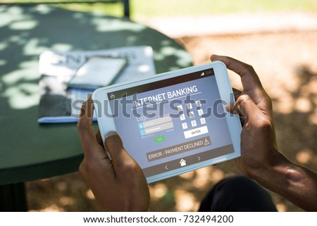 Internet banking text with log in page on phone against man using digital tablet at outdoor restaurant #732494200