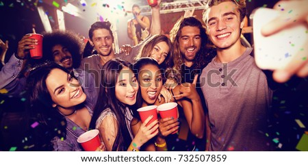 Flying colours against man with friends taking selfie at music concert #732507859
