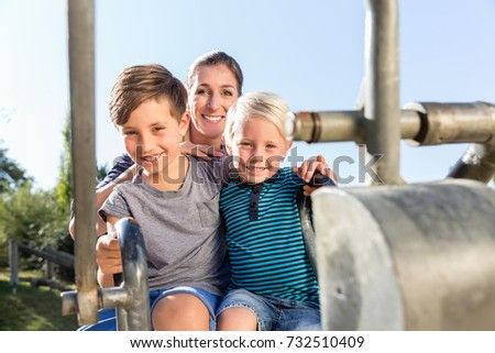 Two brothers playing together at toy excavator on playground outdoors #732510409