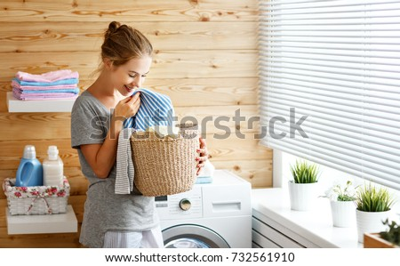 a Happy housewife woman in laundry room with washing machine   #732561910