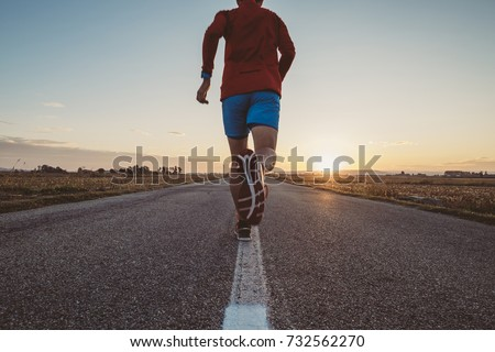Man running on the line on a paved road at the sunrise #732562270