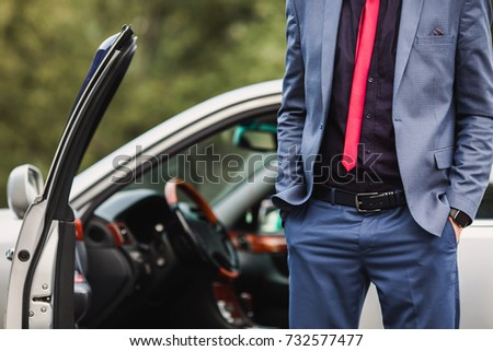 Successful businessman in a dark business suit with a red tie against the background of a car. Stylish man. Fashionable watch on hand. Hand in pocket #732577477