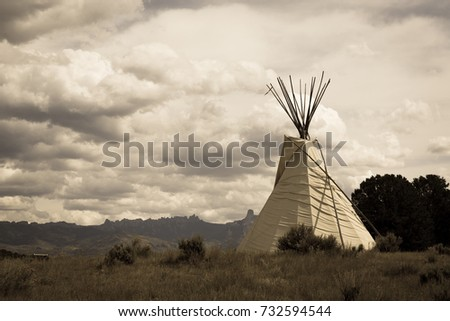 Native American Tee Pee campsite sits alone on the grass field under cloudy sky  with Cimarron Range in background, Colorado.( Aged toned)