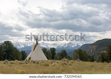 Native American Tee Pee campsite sits alone on the grass field under cloudy sky  with Sneffels Range in background, Colorado.