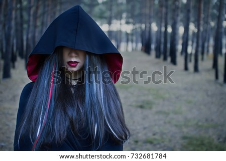 Vampire Woman in a gloomy forest. Beauty Sexy Vampire Girl in a cloak with a hood. Sexy Witch. The eyes are hidden under the hood. Attractive model girl in Halloween costume and makeup. #732681784