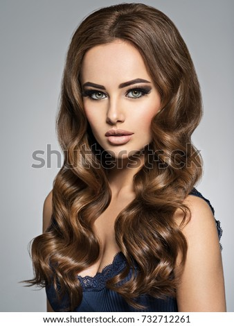 Beautiful caucasian woman with long brown curly hair. Portrait of a pretty young adult girl. Sexy face of an attractive  lady posing at studio over grey background. #732712261