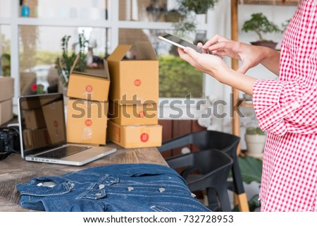 young start up small business owner holding mobile phone and take photo of her product. freelance woman seller use smart phone to take picture and sell cloth on website. Online selling, e-commerce