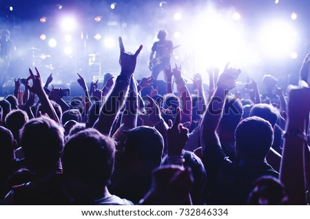 Concert Crowd. Silhouettes young people in front of bright stage lights. Band of rock stars #732846334