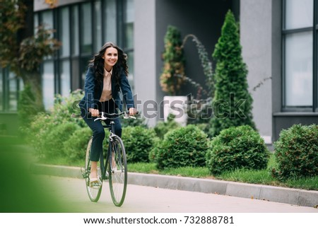 young happy businesswoman riding bicycle Royalty-Free Stock Photo #732888781