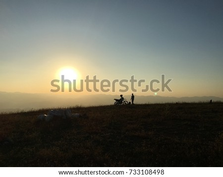 A biker with his motorcycle on top of mountains, looks like he is standing near the sun  #733108498