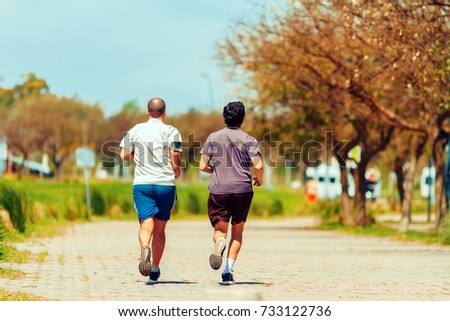 Two men seen from behind run exercise on a path in a park #733122736