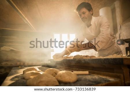 In an artisan bakery, a baker prepare the bread dough. The morning sun comes in through the window #733136839