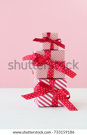 Gift boxes with red bows on pastel pink background