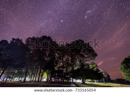 Romantic starry sky night view with guesthouse and campfire.  Camping with spectacular starry sky on mountain with forest. #733165054