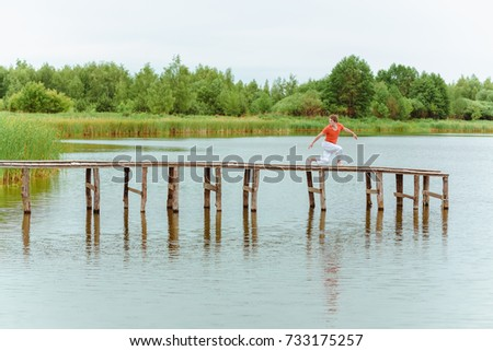 A man doing yoga on wooden pier at the lake #733175257