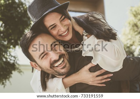 Loving couple have fun in city park. Man carrying woman at piggyback.   #733191559