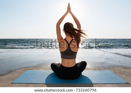 Back view of healthy young sport woman practicing yoga sitting in padmasana at seaside #733260796