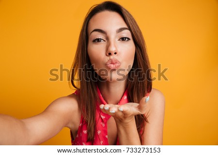 Pretty brunette woman in dress making selfie and sends air kiss at the camera over yellow background