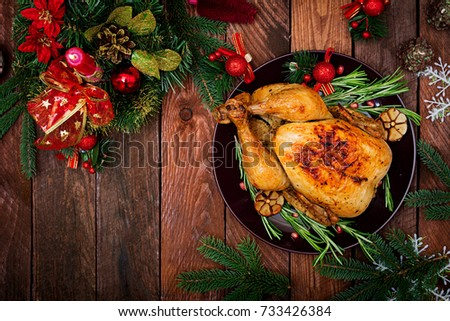 Baked turkey or chicken. The Christmas table is served with a turkey, decorated with bright tinsel and candles. Fried chicken, table. Christmas dinner. Flat lay. Top view #733426384