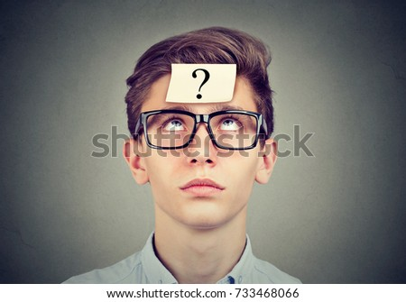 thinking man with question mark looking up on gray wall background #733468066