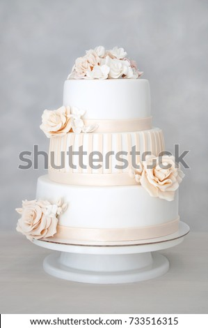 Three-tiered white wedding cake decorated with flowers from mastic on a white wooden table. Picture for a menu or a confectionery catalog.