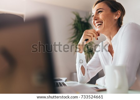 Smiling woman sitting at her desk in office. Happy business woman sitting in office with fingers touching her chin. Royalty-Free Stock Photo #733524661