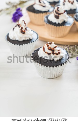 chocolate cup cake with whipped cream on table #733527736