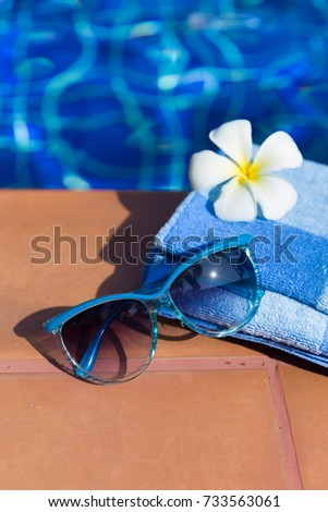 Fluffy towel with sunglasses and flower on border of a swimming pool - holiday tropical concept #733563061