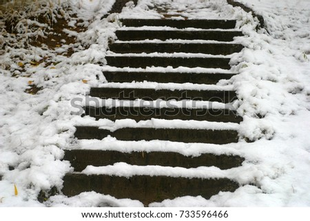 Old gray concrete steps on the hill covered with white snow, drifts with fallen yellow leaves. The first snow in the autumn, in October. Autumn and winter background #733596466