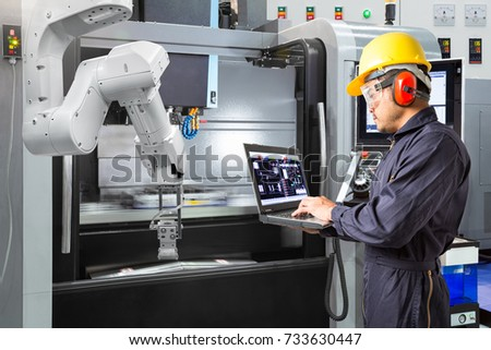 Maintenance engineer using laptop computer control automatic robotic hand with CNC machine in smart factory. Industry 4.0 concept #733630447