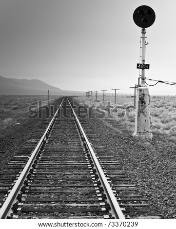 A black and white photograph of an old fashioned railroad light and railroad.