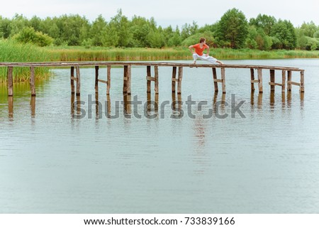 A man doing yoga on wooden pier at the lake #733839166