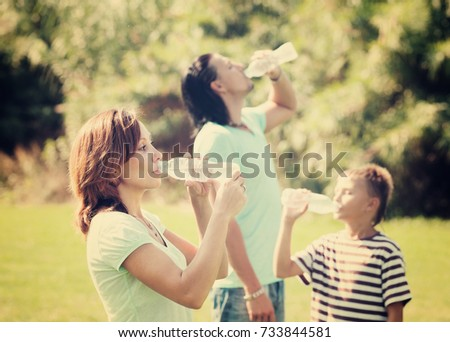 parents with teenager boy drinking clean water from plastic bottles #733844581