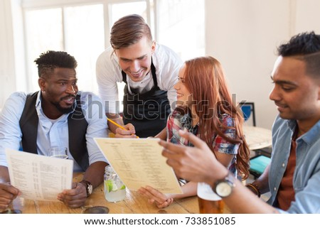 service and people concept - group of happy international friends with menu and drinks and waiter with notepad receiving order at bar or restaurant #733851085