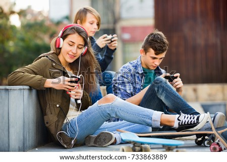 Young cheerful teens playing on smarthphones and listening to music #733863889