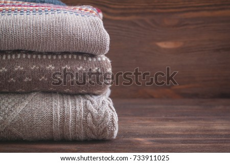 Pile of beige knitted winter clothes on wooden background, sweaters, knitwear, space for text #733911025