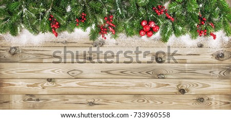 Christmas tree branches with red berries and snow decoration on wooden texture. Winter holidays background
