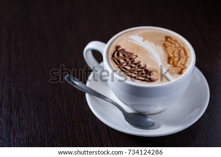 Cup of coffee with a white leaf drawing, and other barista drawings #734124286