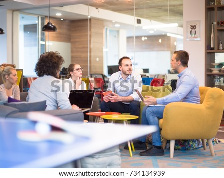 Group of a young business people discussing business plan at modern startup office building Royalty-Free Stock Photo #734134939